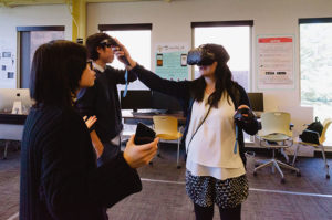 Three students wearing and using virtual reality devices