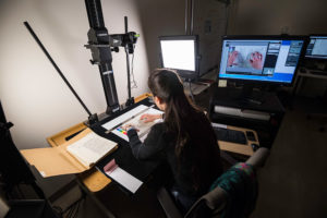 Doctoral student worker Clara Auclair digitizes papers