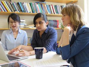 Three women working around a laptop computter