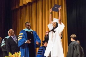female student raising her diploma during East High graduation