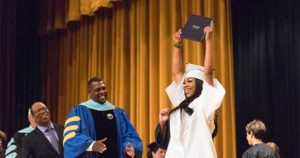 woman holding up diploma during graduation ceremony
