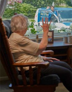 woman in chair waving outside to a man from meals on wheels bringing food