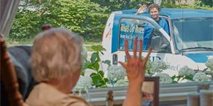 woman in house waving to man delivering meals on wheels