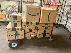 pile of amazon prime boxes on moving cart