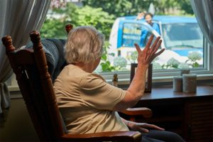 woman waving to man from meals on wheels bringing her food