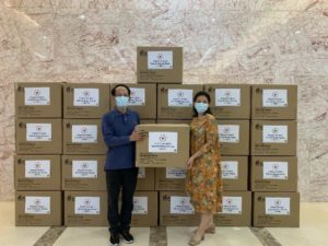 two parents holding boxes of masks while wearing masks themselves