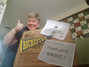 woman giving a thumbs up behind a large box