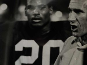 Coach Stark with running back Bob Ford '84 in the background