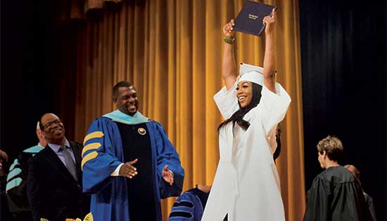 Woman in white cap and gown holding her diploma over her head on stage during graduation